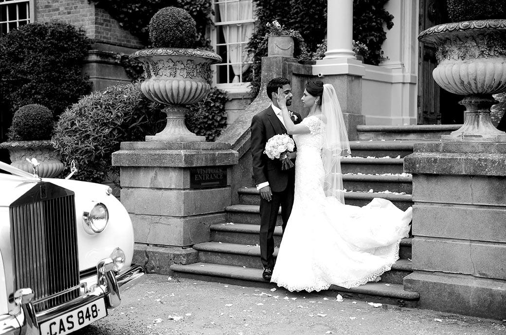 Bride on the front steps of Surrey wedding venue Hampton Court House brushes some confetti of the groom's face in this romantic wedding photograph