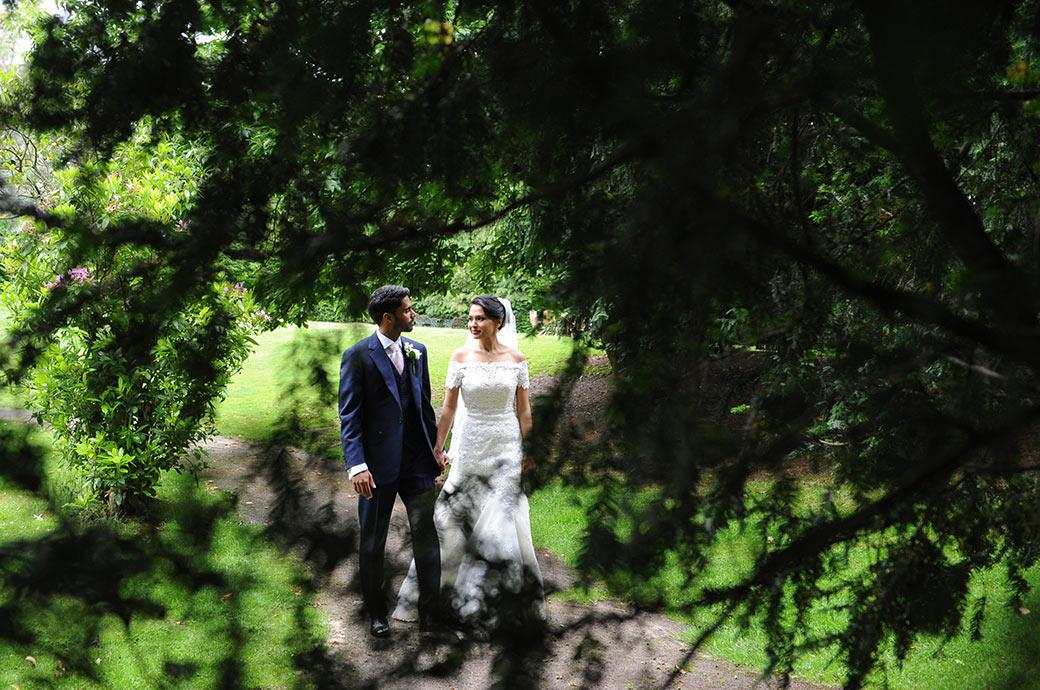 A lovely romantic moment captured at Hampton Court House Surrey wedding venue through tree  branches of newlyweds holding hands and looking into each other's eyes