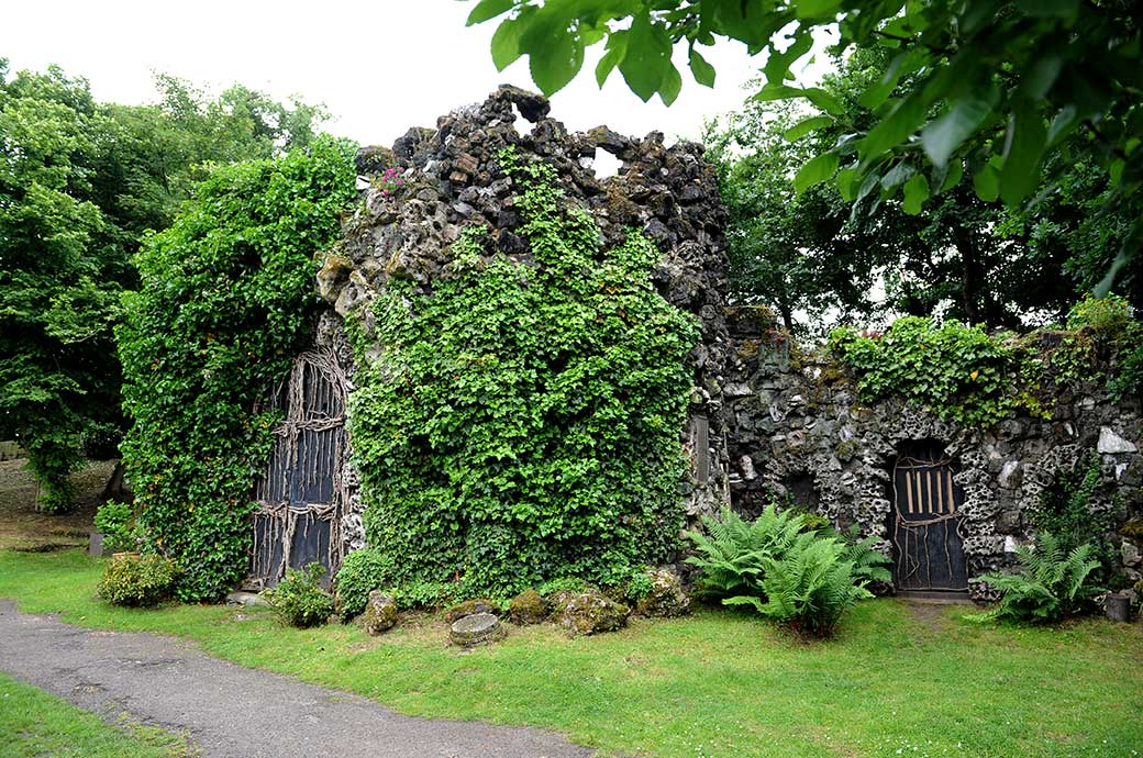 Outside picture taken at Hampton Court House in Surrey of the fascinating and mysterious looking vine covered shell grotto located in the lovely garden grounds beyond the lake