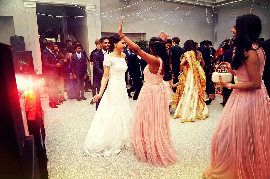 Bride and Bridesmaid have a little fun on the dance floor in the Conservatory captured at the grand and relaxed wedding venue Hampton Court House in Surrey