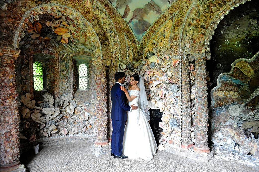 Newlyweds tenderly embrace inside the fascinating and beautifully coloured shell grotto at Surrey wedding venue Hampton Court House