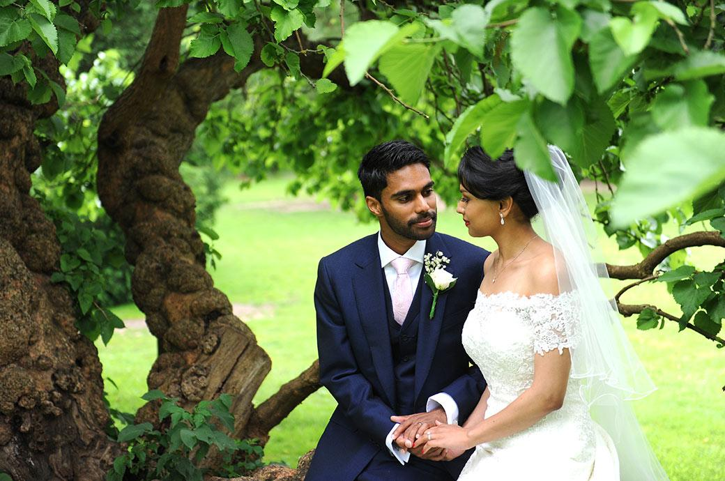 Romantic wedding photograph of the Groom and Bride sharing some time together holding hands and sitting on a tree trunk at Surrey wedding venue Hampton Court House