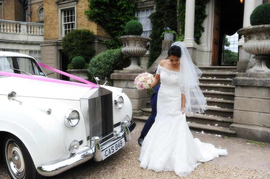 Delicate Bride at Surrey wedding venue Hampton Court House has help from the groom with her wedding dress on the gravel drive  next to their white Rolls Royce