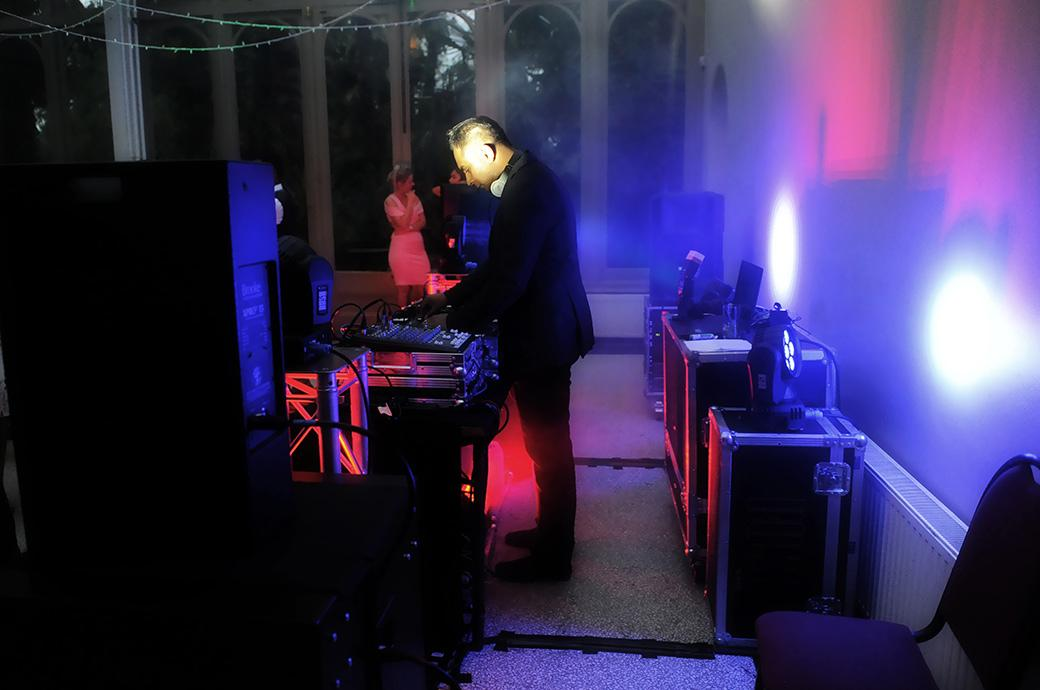 Atmospheric and colourful picture of the wedding DJ behind his decks at Surrey wedding venue Hampton Court House on the dancefloor in the Conservatory