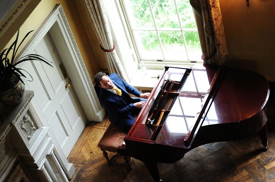 Picture of a pianist playing during the wedding ceremony in the Main Hall at wedding venue Hampton Court House in Surrey captured looking down from the first floor
