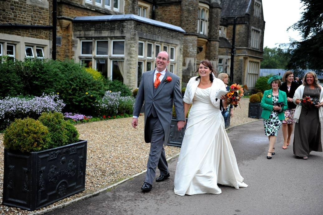 Happy Groom captured in this wedding picture as he escorts his wife to the surprise wedding bus parked outside at the front of Surrey wedding venue Hartsfield Manor
