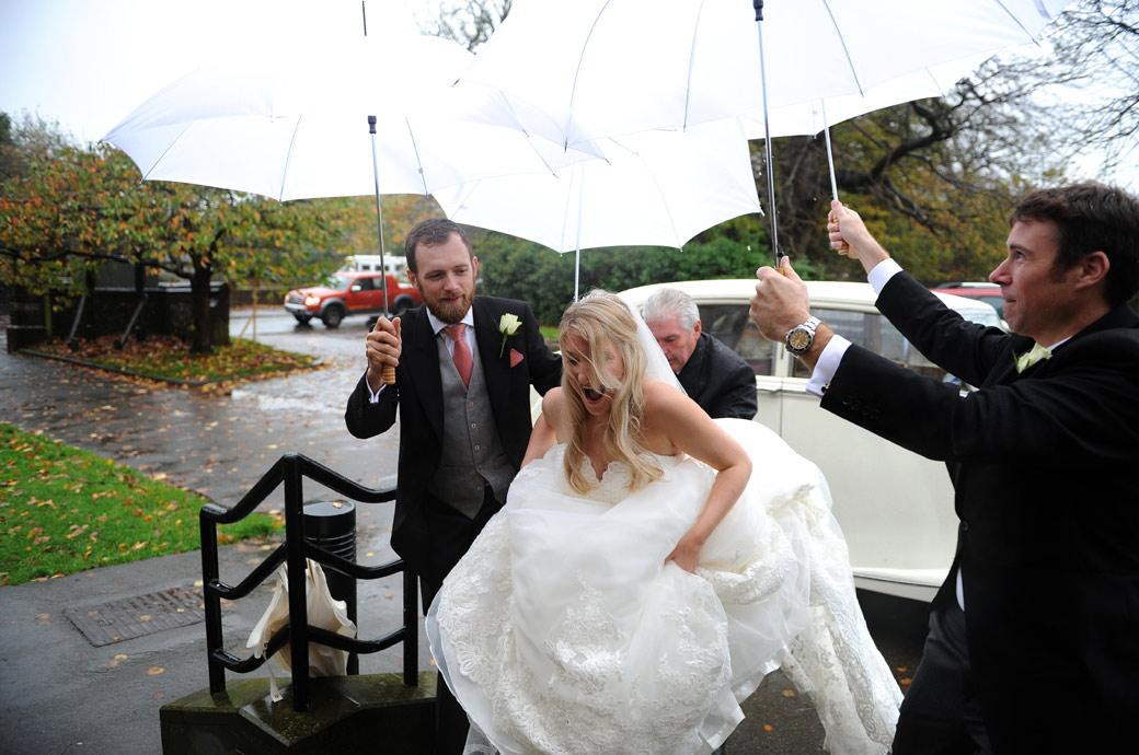Great wedding photo of the Bride picking up her dress protected by ushers with white umbrellas on a rainy day for her marriage and reception at Church and Hartsfield Manor Surrey