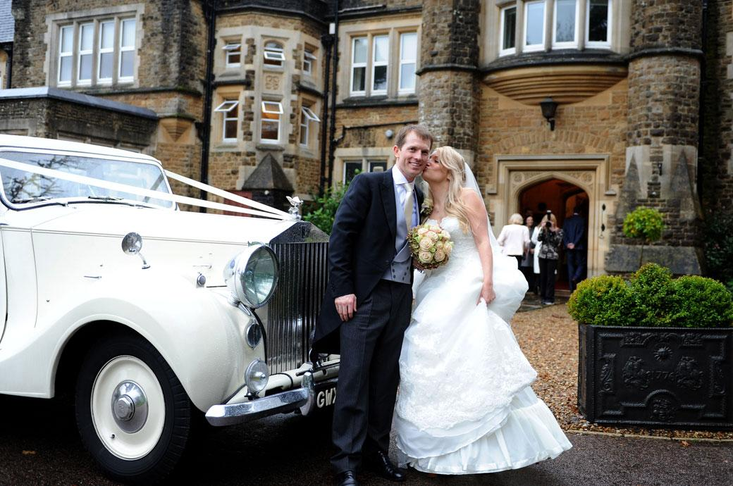 Sweet wedding photograph of a Bride kissing her Groom as they stand by their Rolls Royce wedding car outside Hartsfield Manor taken by two Surrey Lane wedding photographers