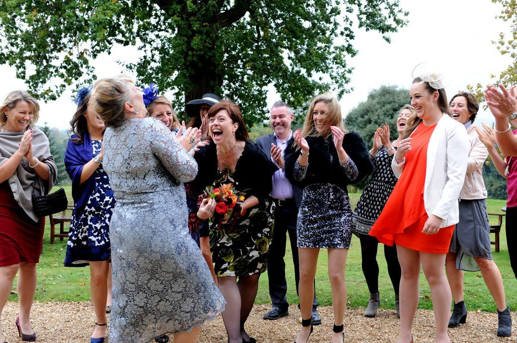 Fun wedding photo of the smiles and applause as one of the ladies at Hartsfield Manor in Surrey catches the Bride's bouquet as it's thrown over the terrace