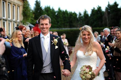 Smiling Bride and groom captured in this wedding photo as they brave the confetti throwing out on the patio at the relaxed Surrey wedding venue Hartsfield Manor