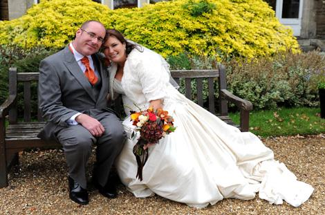 Relaxed newlyweds sitting romantically on a bench together in the large garden area at Hartsfield Manor in Betchworth captured by Surrey Lane wedding photographers