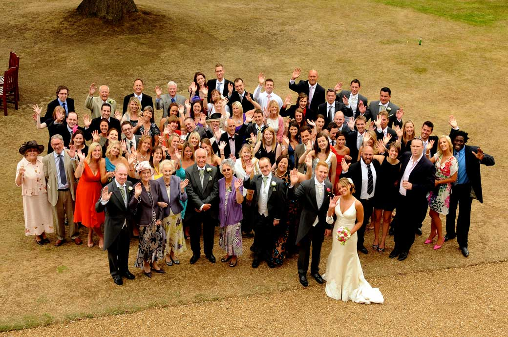 A fun everyone waving at the photographer wedding picture take on a parched lawn at the Hartsfield Manor Surrey wedding venue