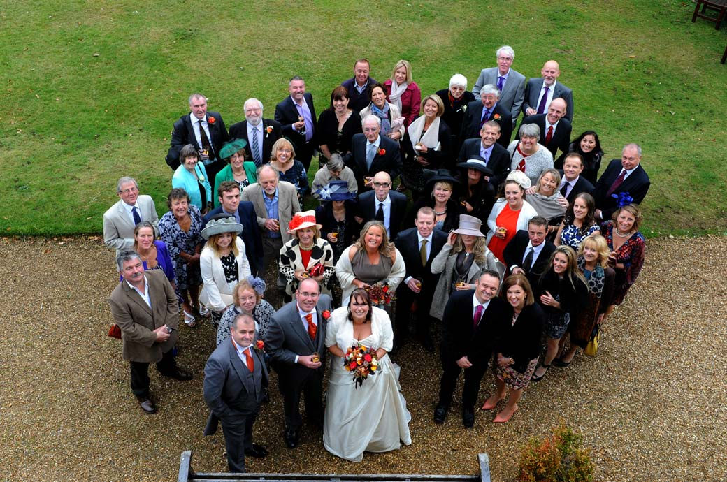 Everyone at the winter wedding looking up to the Surrey Lane wedding photographer leaning out of a top window for this classic  Hartsfield Manor wedding photo