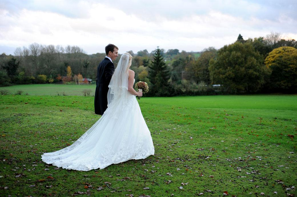 Newlyweds walk across a wet green lawn to see the beautiful autumnal view from the hill in Surrey at the Hartsfield Manor wedding venue in Betchworth