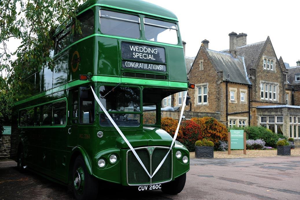 Green vintage green wedding bus parked outside the grand and welcoming Surrey wedding venue Hartsfield Manor awaiting the Bride and Groom and their guests