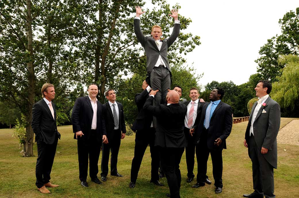 Boys having fun as the Groom is lifted up for a mock Rugby line out photo captured at a Hartsfield Manor Surrey wedding reception