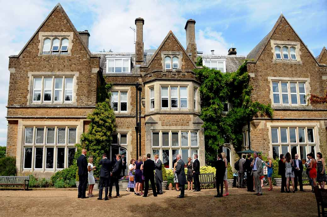 Guests relaxing and chatting at the back garden of the grand Victorian Surrey wedding venue in Betchworth that is Hartsfield Manor