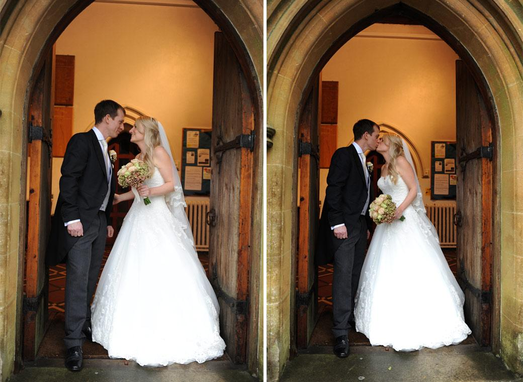 Romantic wedding pictures of the newlyweds standing in the doorway of the church before leaving for the reception at surrey wedding venue Hartsfield Manor on a wet winter day