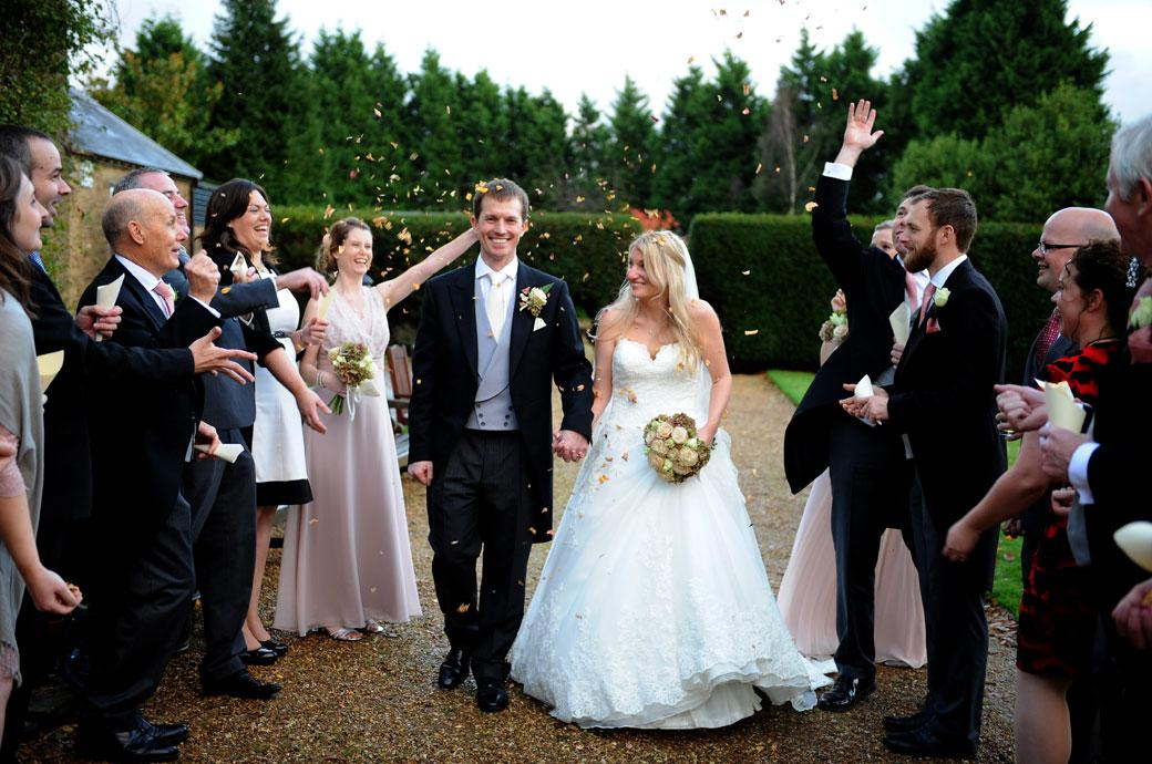 Lots of fun and smiles as guests throw confetti over the happy Bride  and Groom as they walk along the terrace at Hartsfield Manor captured by a Surrey Lane wedding photographer