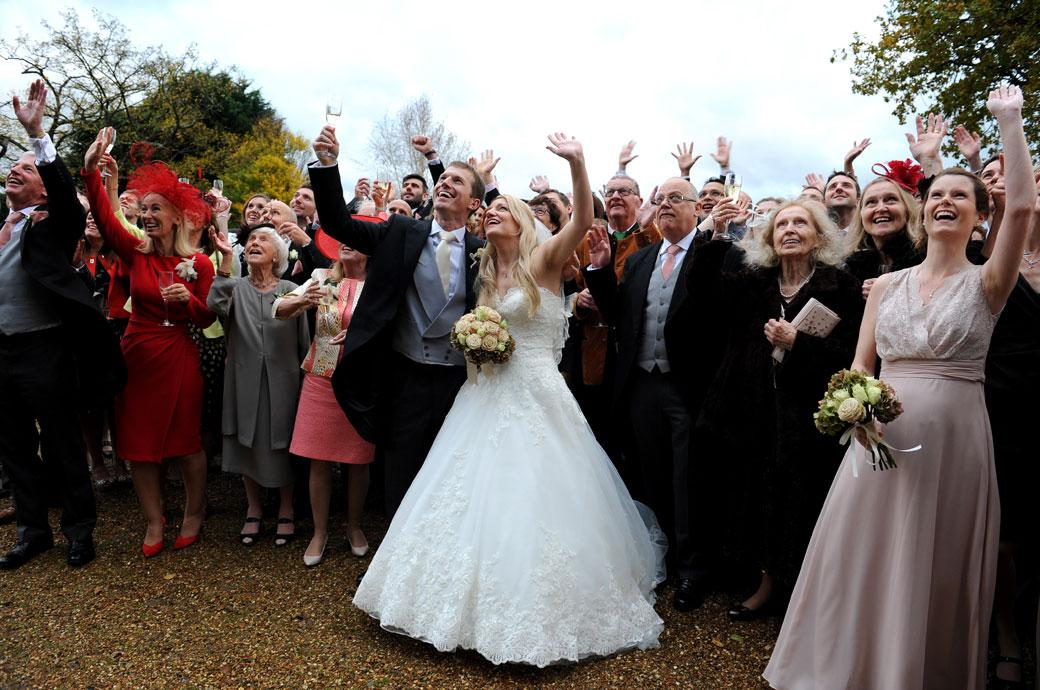 Close up of the Bride and groom and lots of smiling faces  with champagne glasses in hands  as they wave upwards for a picture at Hartsfield Manor a great wedding venue in Surrey