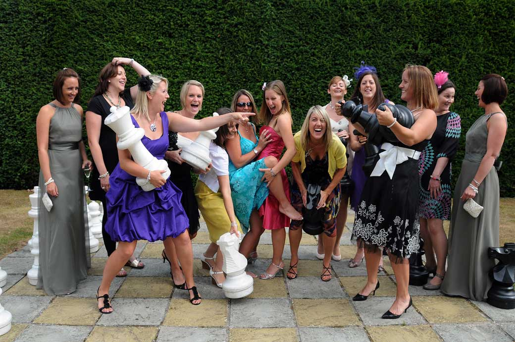 A great wedding photograph of the Bride's Hockey ladies having a lot of fun with the giant chess pieces at a wedding in Hartsfield Manor Surrey