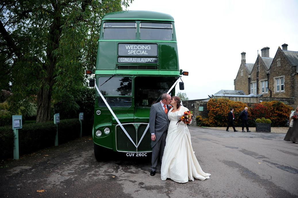 Newlyweds kiss in front of the green vintage wedding special bus parked outside Hartsfield Manor, Betchworth captured by a Surrey Lane wedding photographers