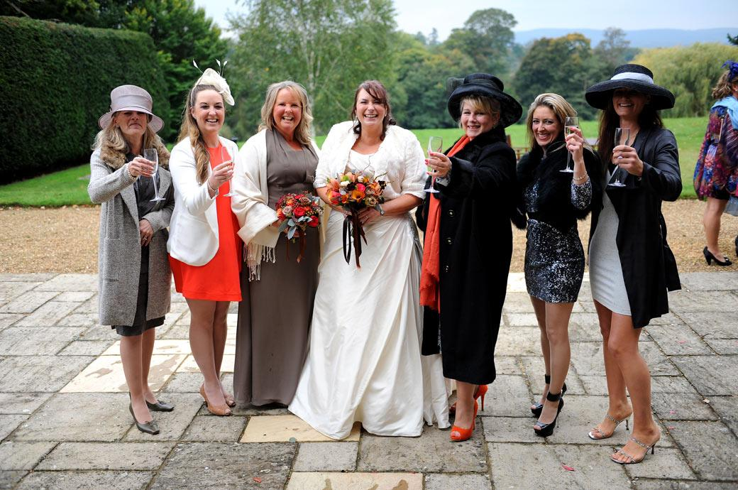 Bride smiles as her wine club ladies all raise their glasses to the Surrey Lane wedding photographers out on the terrace  at Hartsfield Manor on a fine  autumnal wedding day