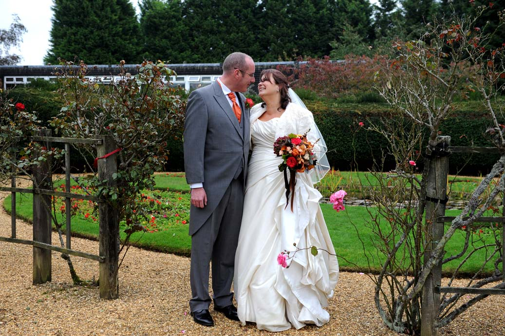Loving looks for the happy couple as they stand in the rose garden in this autumnal wedding picture taken at the popular Surrey wedding venue Hartsfield Manor in Betchworth