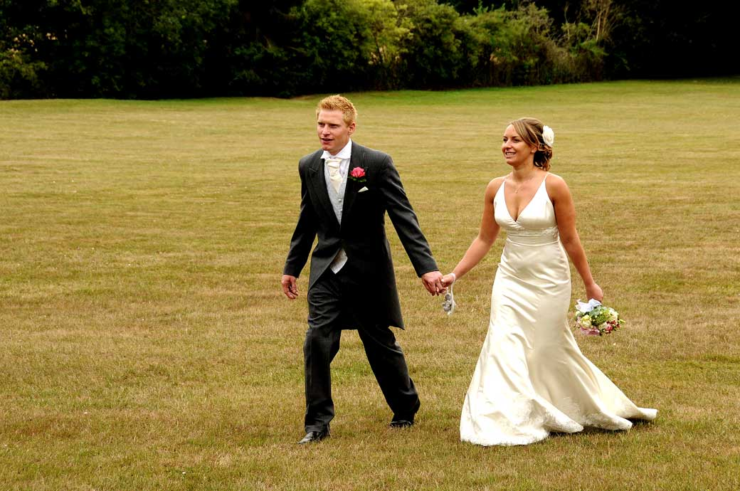 Wedding couple walking hand in hand photograph taken on the parched back lawn at Hartsfield Manor Surrey