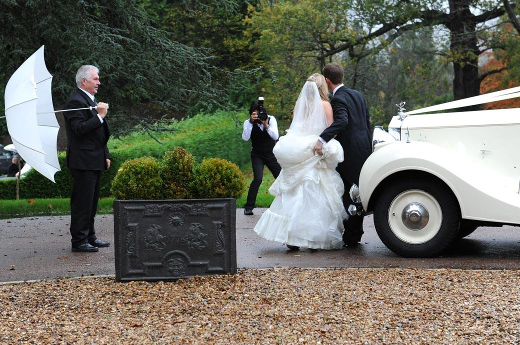 Action wedding picture of a Surrey Lane wedding photographer at Hartsfield Manor photographing the newlyweds by their Rolls Royce as the chauffeur holds up an umbrella
