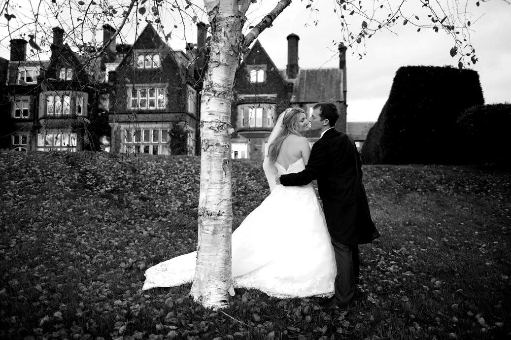 Lovers romantically embrace by tree on the lawn on a wet autumnal wedding day at the lovely Hartsfield Manor in Betchworth a Surrey wedding venue of renown