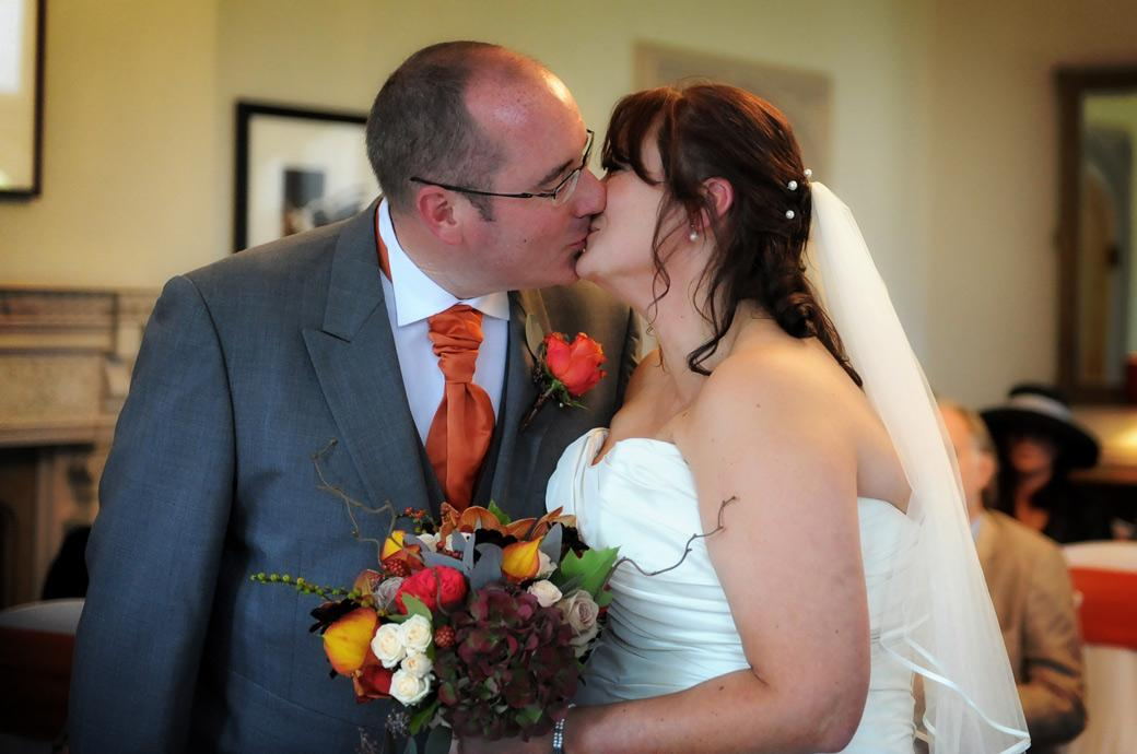 Wedding picture of the newlyweds as they romantically kiss after being announced husband and wife at the grand but relaxed Surrey wedding venue Hartsfield Manor