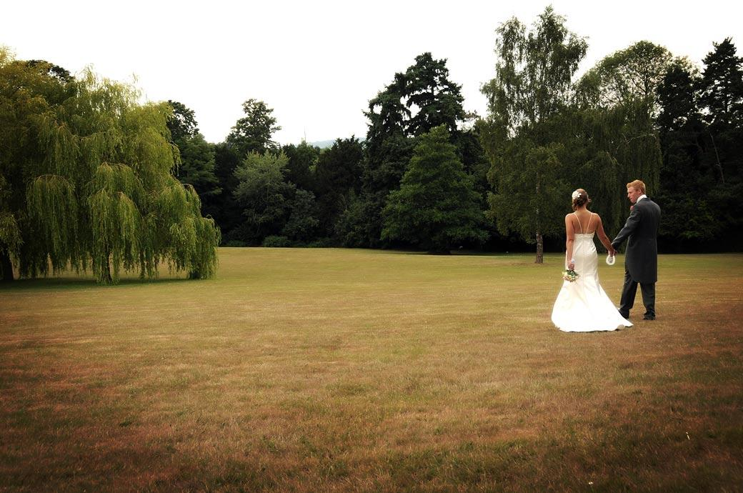 A romantic wedding couple picture taken as they walk across the lawn to the trees taken at Hartsfield Manor, Betchworth, Surrey