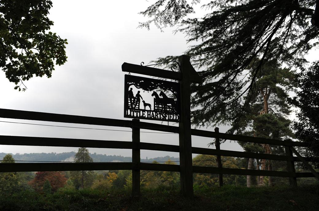 Little Hartsfield silhouette sign post depicting a rural scene located at the beginning of the long tree lined drive to Surrey wedding venue Hartsfield Manor in Betchworth