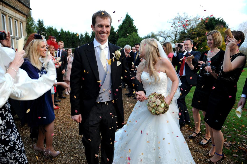Smiles amongst the confetti throwers as the couple reach the end of the long line on the terrace at Hartsfield Manor captured by Surrey Lane wedding photographers