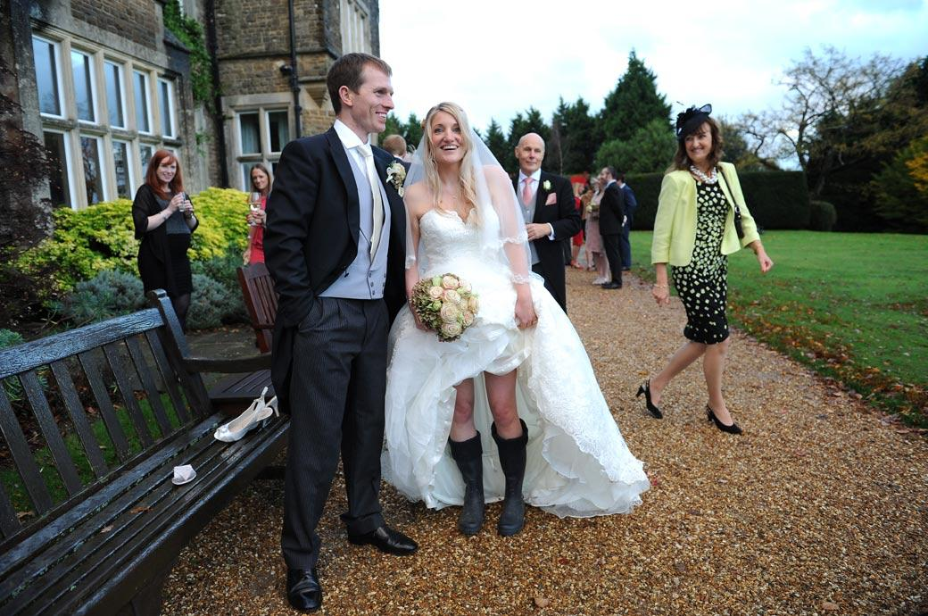 Funny wedding photograph of a smiling Groom and Bride as the Bride shows off her wellies ready for a walk at Surrey wedding venue Hartsfield Manor during a wet autumn day