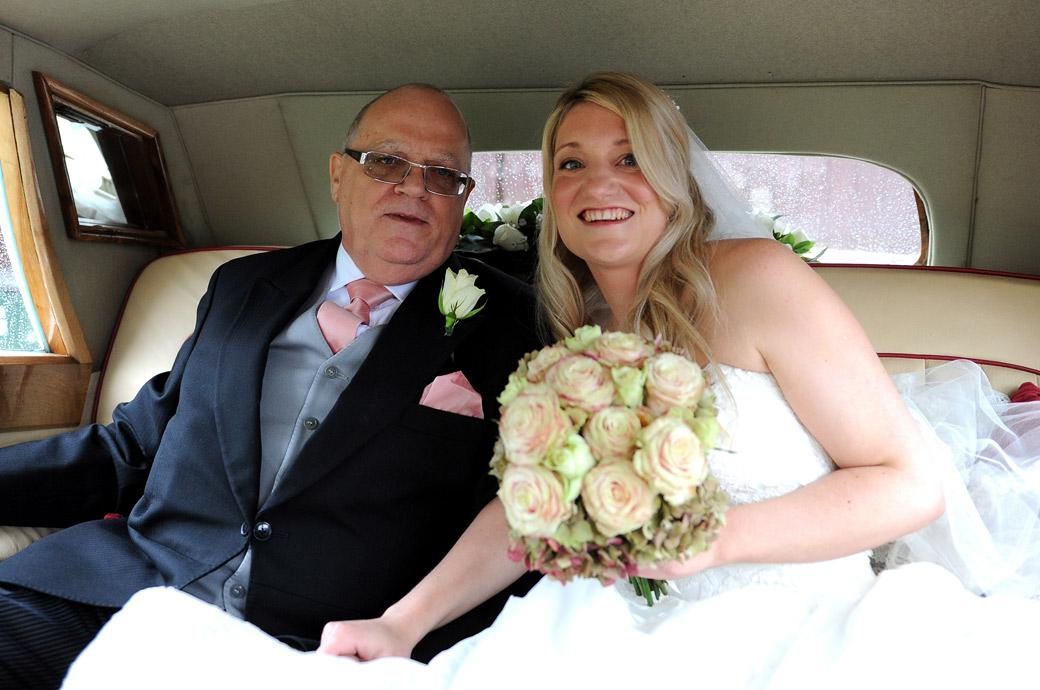 A happy smiling Bride sits with her father on the way to the church wedding followed by a reception at Hartsfield Manor captured by Surrey Lane wedding photographers