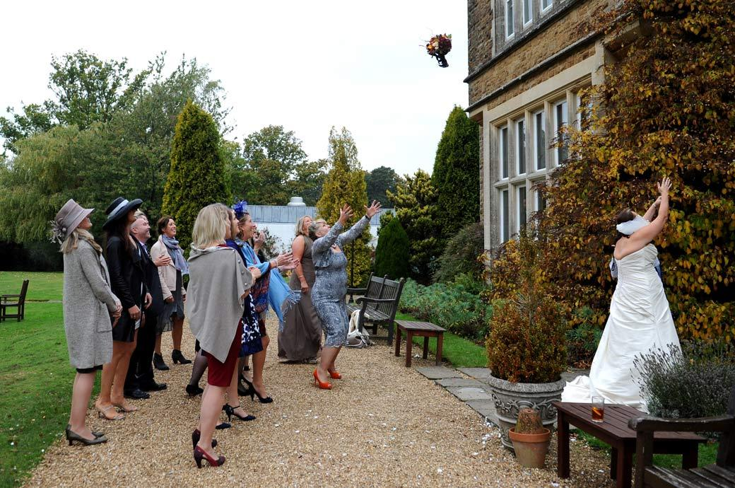 Bride throws her bouquet to the awaiting ladies on the terrace in this fun wedding photograph taken in Hartsfield Manor, Surrey in Betchworth village