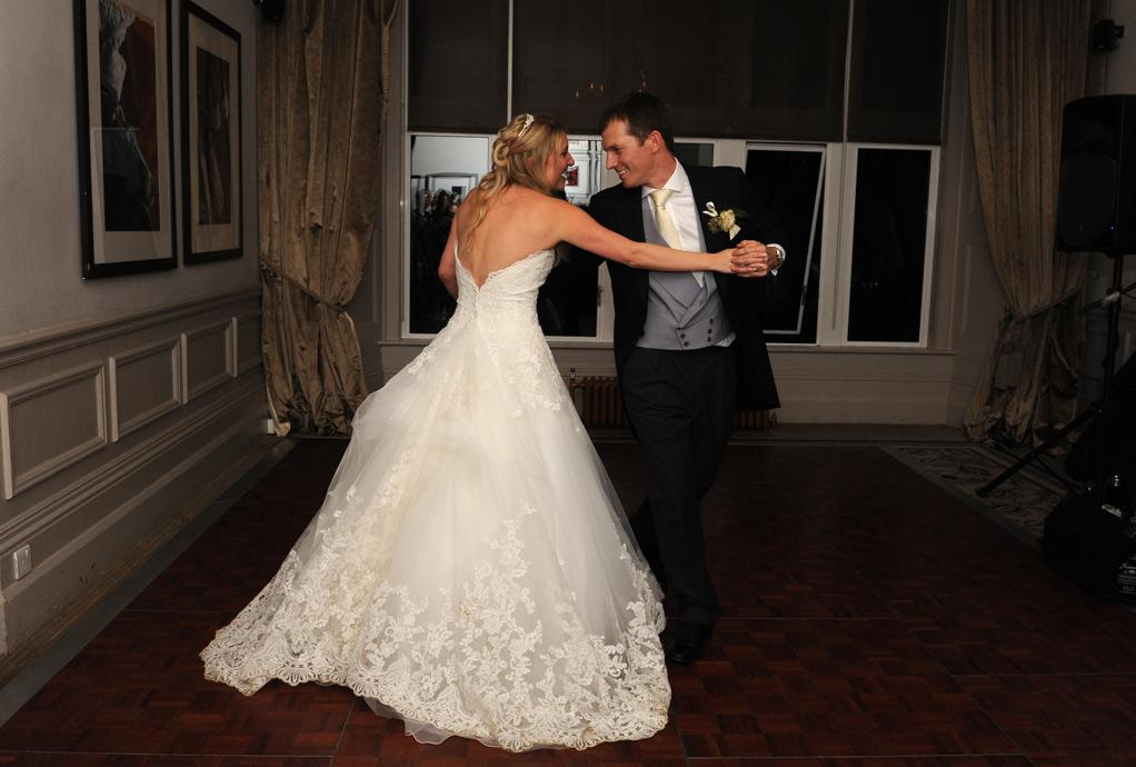 Happy newlyweds at Hartsfield Manor, Betchworth in Surrey enjoying their practised dance moves during their first dance on the Terrace Room dance floor