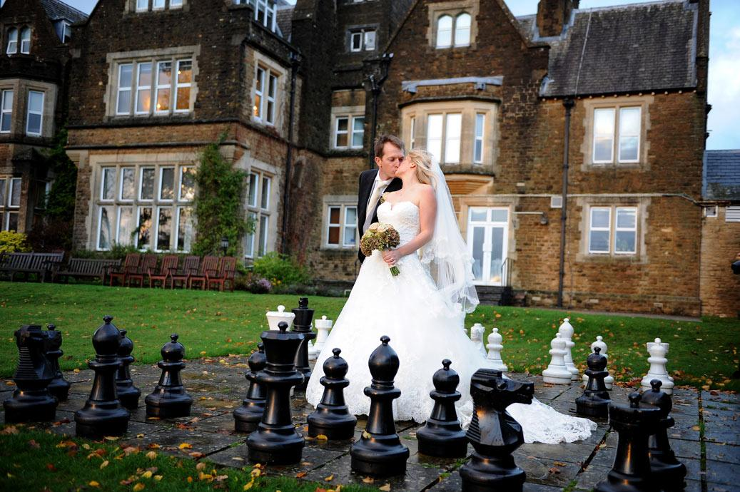 Bride and Groom kiss dramatically on the giant garden chessboard on a wed autumnal wedding day at Hartsfield Manor, a fine Surrey wedding venue in Betchworth