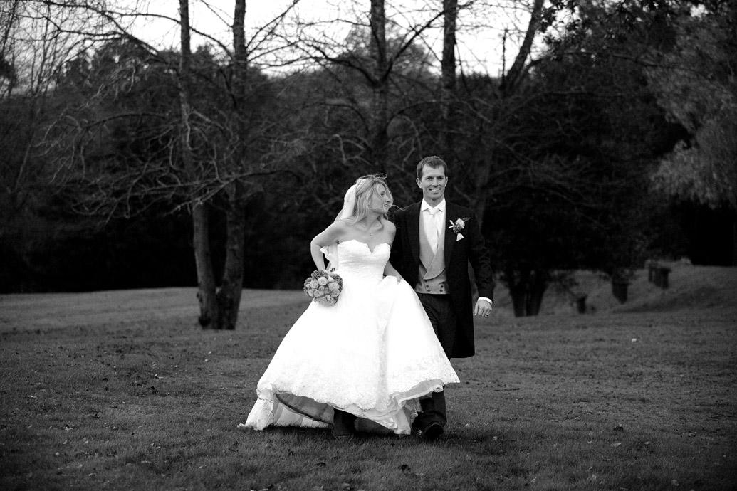 A smiling Groom leads his lovely wife in her beautiful wedding dress across the lawn at Surrey wedding venue Hartsfield Manor on a wet autumnal wedding day