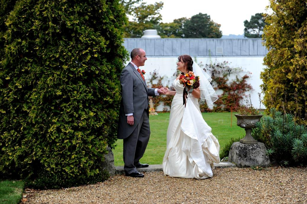 Bride and Groom at the popular Surrey wedding venue Hartsfield Manor romantically hold hands and look into each others eyes in the garden after getting married