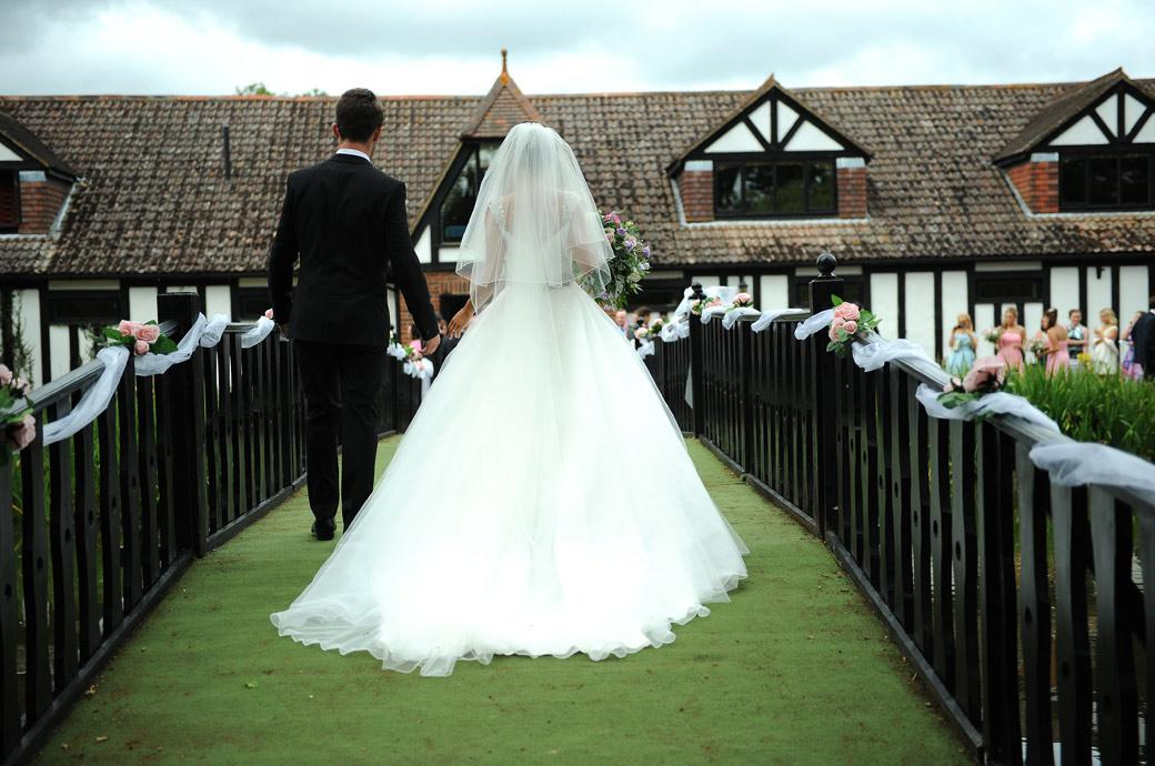 The Bride and Groom walk across the ornamental pond bridge at Kent wedding venue Hever Castle Golf Club captured in this wedding photo taken from behind by a Surrey Lane wedding photographer