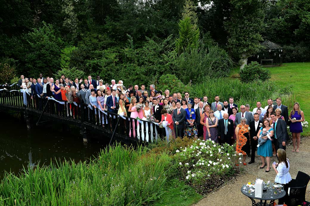 Everyone standing on the bridge over the Hever Castle Golf Club ornamental pond for the classic big group wedding picture captured by a Surrey Lane wedding photographer