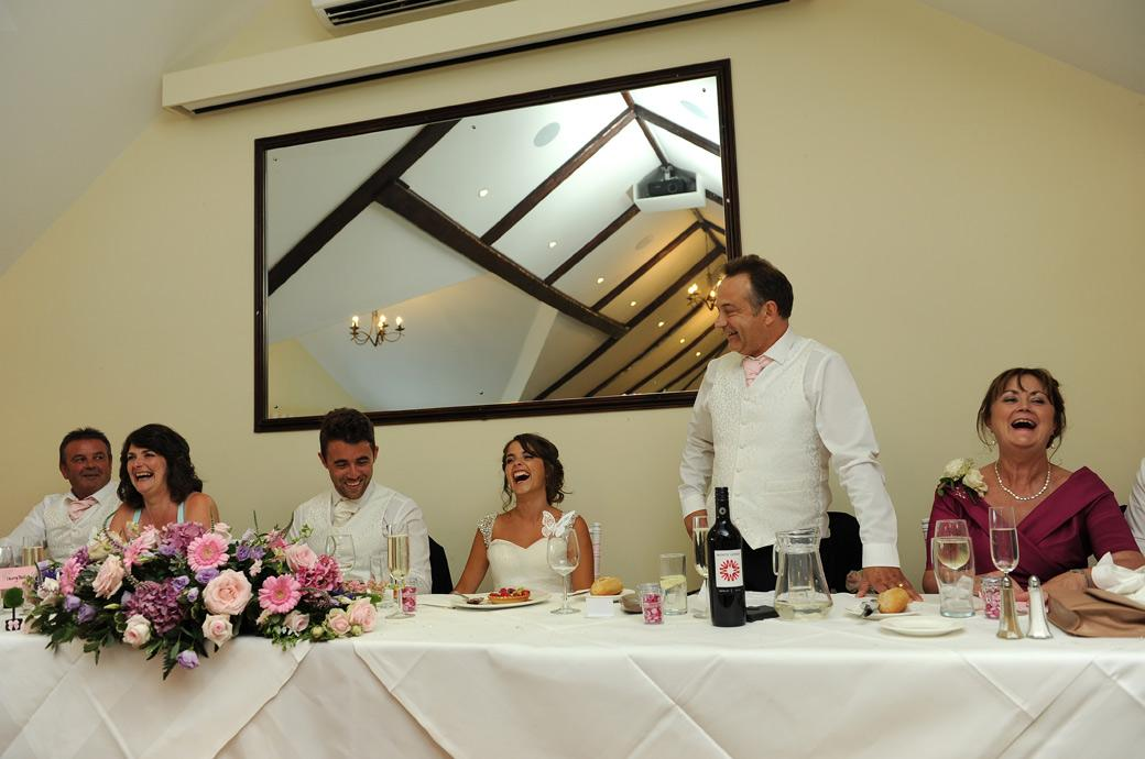 Father of the Bride makes the Top Table laugh as he makes a joke during the speeches in this wedding photograph captured in the Princes Suite at Hever Castle Golf Club a fine Kent wedding venue