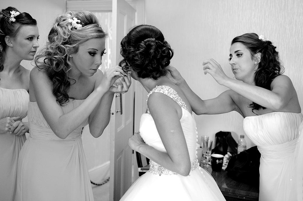 Bridesmaids busy adjusting the Bride's ear rings in a wedding photograph taken prior to a marriage at Kent wedding venues St Paul's Church Four Elms and Hever Castle Golf Club