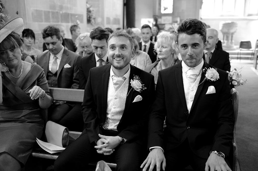 Groom trying to keep a straight face as he listens to his Best Man in this funny wedding picture from Kent wedding venue St Paul's Church Four Elms and later at Hever Castle Golf Club