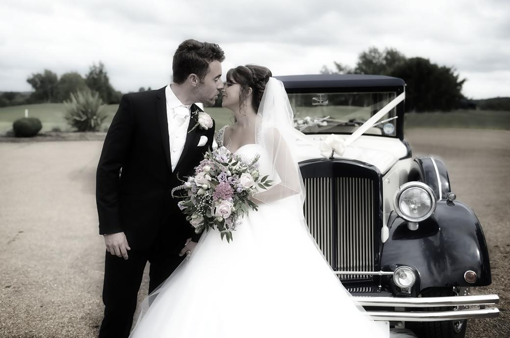 A lovely newly-wed couple kiss by the bridal car at Hever Castle Golf Club captured in this wedding picture by Surrey Lane wedding photographers