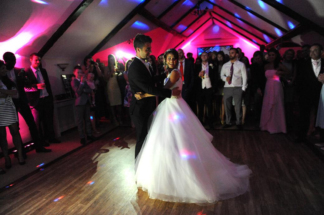 Fun on the dancefloor for the Bride as she partakes in the first dance with her husband in this relaxed wedding photo from Hever Castle Golf Club a fun and informal Kent wedding venue