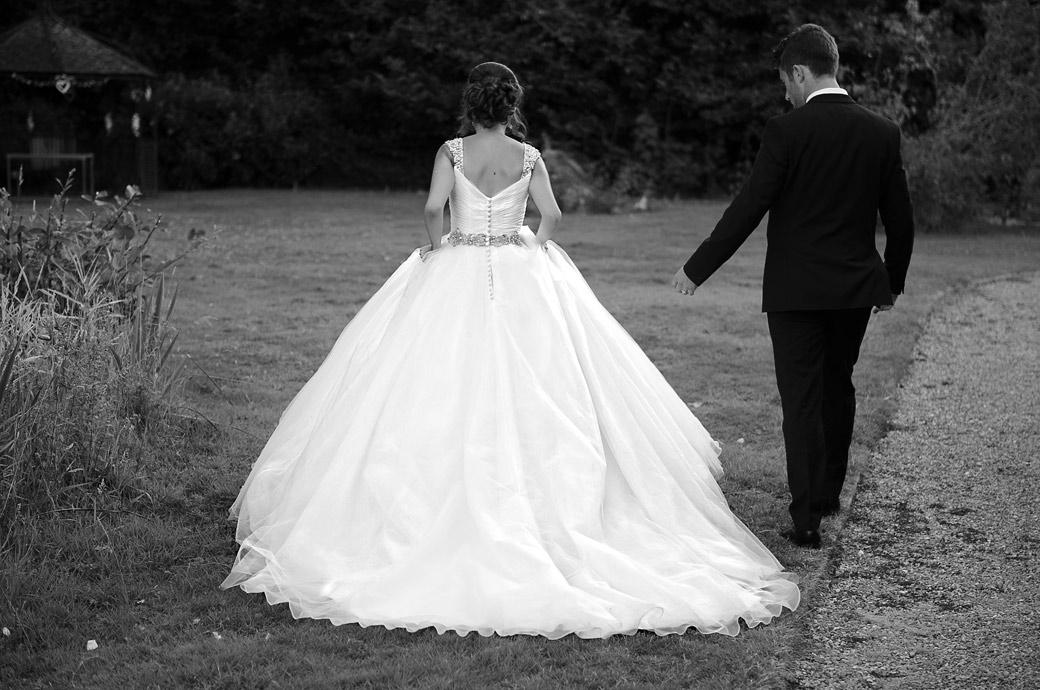The Groom and his Bride in her beautiful dress captured in this wedding picture at the Kent wedding venue Hever Castle Golf Club as they walk towards the gazebo for some romantic wedding photos